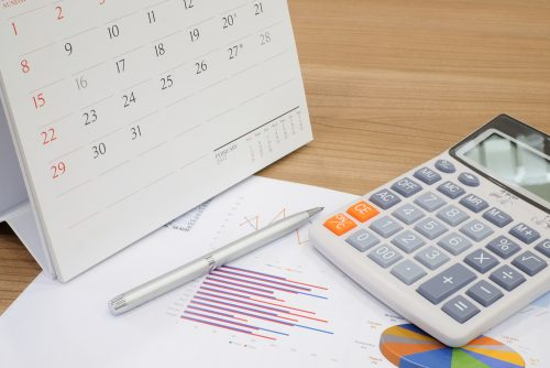 A calculator, calendar, and pen for calculating taxes